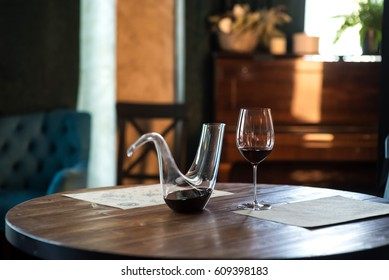 Decanter with red wine and glass on wooden table in interior. Free space for text. Still life style
