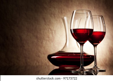 decanter with red wine and glass on a old stone background