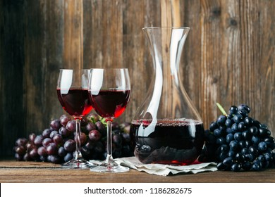 Decanter, red wine and two glasses, grapes, wooden background