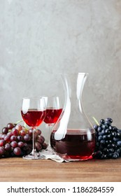 Decanter, red wine and two glasses, grapes, gray stone wall, background