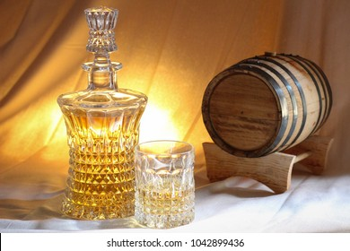 A decanter and rocks glass set next to an oak aging barrel