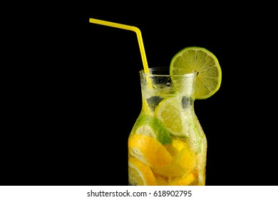Decanter with soda water, lemons, limes and a yellow straw on a black background.