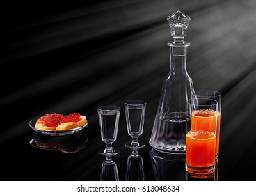 Decanter and two shot glasses with ice vodka, two salmon red caviar sandwiches on a glass plate and two glasses with multifruit juice on a black acrylic surface