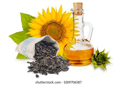 Decanter with vegetable oil, pouch with seeds, flower and green sunflower leaves isolated on white background