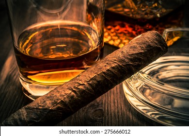Decanter of whiskey and a glass with cuban cigar on a wooden table. Image vignetting and the orange-blue toning