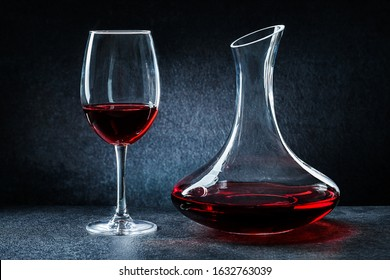 decanter and wineglass with red wine on black background