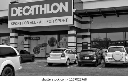 Decathlon store. French sporting goods retaile. Shopping mall in Accra. Active style. Cars in a parking lot. Development of marketing in West Africa. Black White Photo Ghana, Accra – January 20, 2017