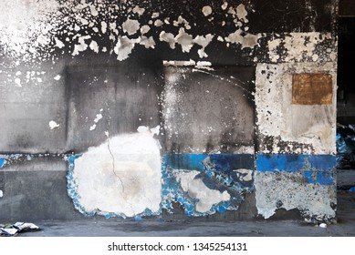 Decay concrete wall in abandoned factory partially covered by soot marks after fire. Smoke runs industrial background.