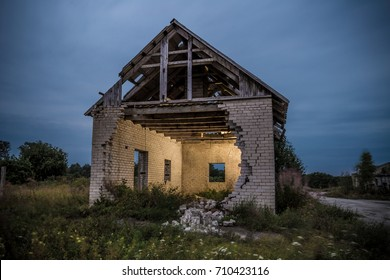 Decayed house with fallen wall and inside lit up by flash