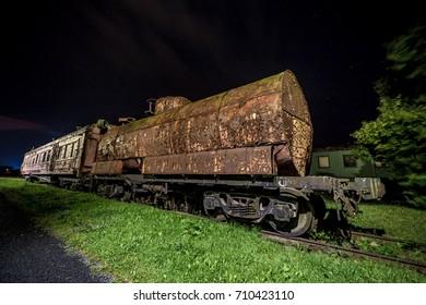 Decayed locomotive car at night