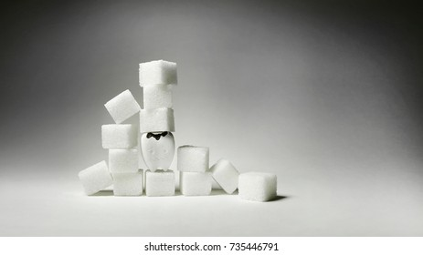 Decayed teeth among Heap of cubes sugar, if you eat sweet a lot it will be decayed teeth