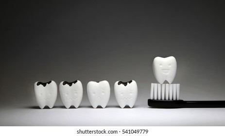 Decayed tooth  and Tooth model in happy emotion on black toothbrush, if brush the teeth, teeth will good healthy 2