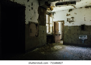 A decaying bathroom with peeling paint and crumbling plaster inside a long abandoned hospital.