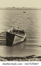 Decaying boat in the water by the footpath along the Ore Estuary, Orford, Suffolk, UK. Grainy antique vintage sepia effect.