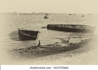Decaying boats in the water by the footpath along the Ore Estuary, Orford, Suffolk, UK. Grainy antique vintage sepia effect.