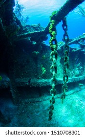 A decaying chain hangs from some structure in a sunken shipwreck. The rusting metal underwater provides a habitat for marine life and is also enjoyable for scuba divers to see