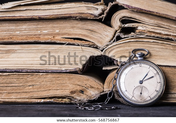 Decaying clock on the background of old shabby wise books.