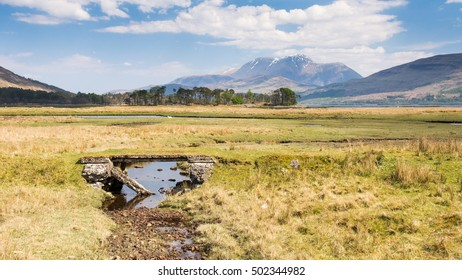 A decaying old concrete bridge accross the salt marsh of Iverscaddle Bay in the West Highlands of Scotland, with Ben Nevis mountain rising in the distance.