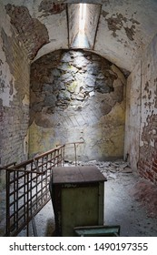 Decaying prison cell at an abandoned prison. Sunlight shining down on the ground. Abandoned furniture and crumbling walls.
