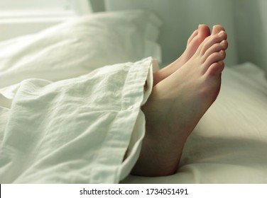 Deceased person covered in a white sheet on a hospital bed.