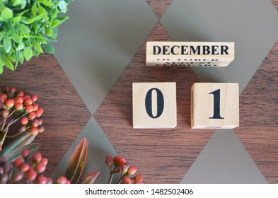 December 1. Date of December month. Number Cube with a flower and leaves on Diamond wood table for the background