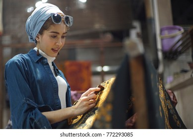 December 10 2017 Surakarta - Indonesia : Woman drawing of batik, canting batik on the fabric, is motive culture of Surakarta Indonesia