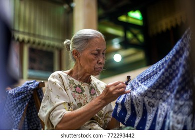 December 10 2017 Surakarta - Indonesia : Old Woman making of batik, canting batik on the fabric blue color, is motive culture of Surakarta Indonesia