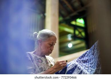 December 10 2017 Surakarta - Indonesia : Old Woman making of batik, canting batik on the fabric blue color, is motive culture of Surakarta Indonesia