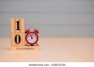 December 10th set on wooden calendar and red alarm clock with blue background. Clock showing five minutes to midnight