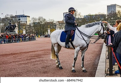 December 17, 2015. Buckingham Palace, London. Friendly mounted police officer and her horse chatting with crowds lining up to see the changing of the guards.