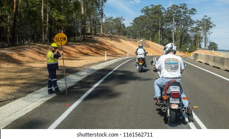 """December 18 2017: Tilba, Victoria, Australia- December 18 2017: Road construction site on Princes Highway A1. A worker is giving way to the traffic with a """"Slow"""" sign."""