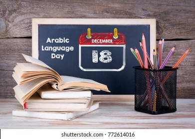 December 18. UN Arabic Language Day. Stack of books, chalk blackboard with pencils on the wooden table