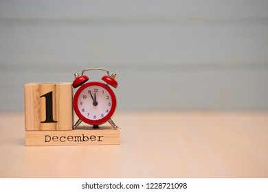 December 1st set on wooden calendar and red alarm clock with blue background. Clock face showing five minutes to midnight