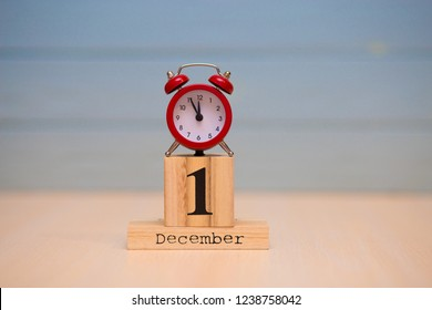 December 1st set on wooden calendar and red alarm clock with blue background. Clock showing five minutes to midnight
