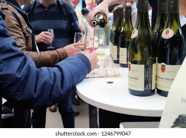 December 2, 2018- Porte de Versailles, Paris, France : Wine tasters with hands of seller pouring red wine into glass, in Independent winemakers of Fr ance(Salon du vin) celebrateth 40 years in 2018