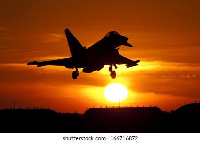 December 2013. First Tranche 3 Eurofighter Typhoon flies; Seen here is late production Tranche 2 aircraft flying with No 29 Squadron. Landing at RAF Coningsby against a setting sun in silhouette