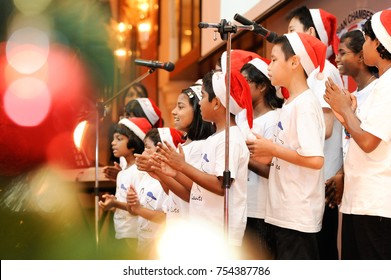 December 2016,Kuala Lumpur,Malaysia.Selective focus on a group of Kids Choir wearing christmas  santa claus hats at Christmas dinner party event at a Christmas celebration.