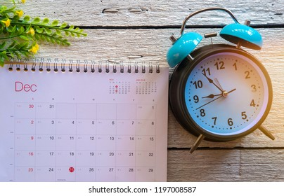 December 2018 calendar AND BLUE RETRO ALARM CLOCK on white wooden background. Winter time and mood