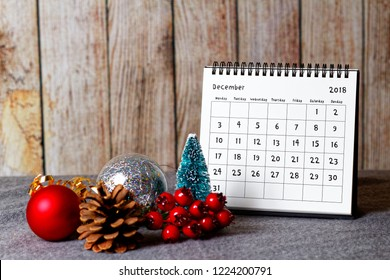 December 2018 calendar and Christmas decoration - baubles, cone and rowanberry on the soft table and wooden wall in the background