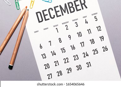 December 2020 simple calendar with office supplies and copy space