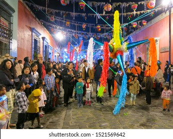 December 21 2018 - Oaxaca Mexico - Mexican children breaking a piñata, a brightly decorated paper container filled with candy and toys.  Christmas pinatas are often shaped as seven-pointed stars.