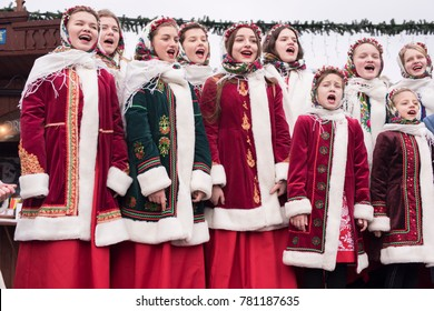 DECEMBER 24, 2017 - KRAKOW, POLAND:   Polish children dressed in traditional costume singing Christmas carols to a gathering of people in the Main Market Square in Old Town, Krakow, Poland.
