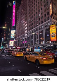 December 24, 2017, New York, USA. Famous area of Times Square, with its typical lights during the night, buildings with luminous signs, people walking and famous yellow taxis of New York.