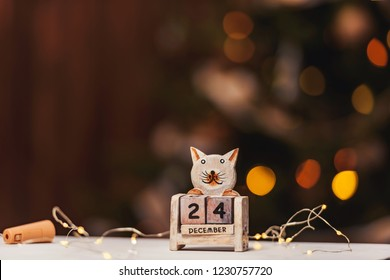 December 24th on the perpetual calendar. Perpetual calendar on a background of bokeh garlands. Christmas on the calendar. Christmas Eve, the night before Christmas.