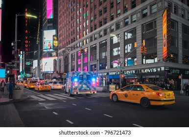 December 25, 2017, New York, USA. Times Square shopping area at night. Yellow cabs and ambulance. People walking and doing their Christmas shopping