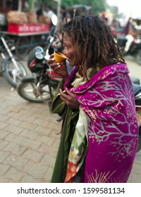 December 25, 2019 at Mau District of Uttar Pradesh -One beggar woman is having tea and smoking cigarette with torn clothes standing in the market on a chilly winter day; representing poverty concept.