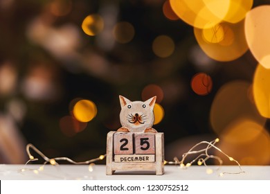 December 25th on the perpetual calendar. Perpetual calendar on a background of bokeh garlands. Christmas on the calendar
