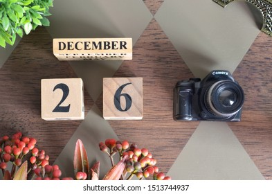 December 26, Date design with Number cube, a flower and camera on Diamond wood background.