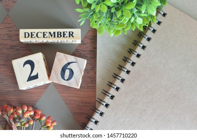 December 26. Date of December month. Number Cube with a flower and notebook on Diamond wood table for the background.