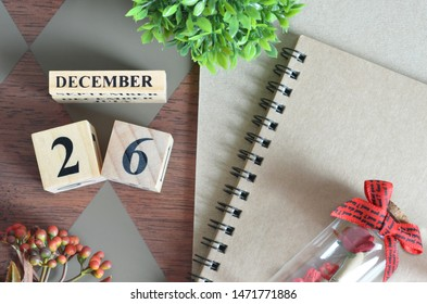 December 26. Date of December month. Number Cube with a flower, Rose bottle and notebook on Diamond wood table for the background.